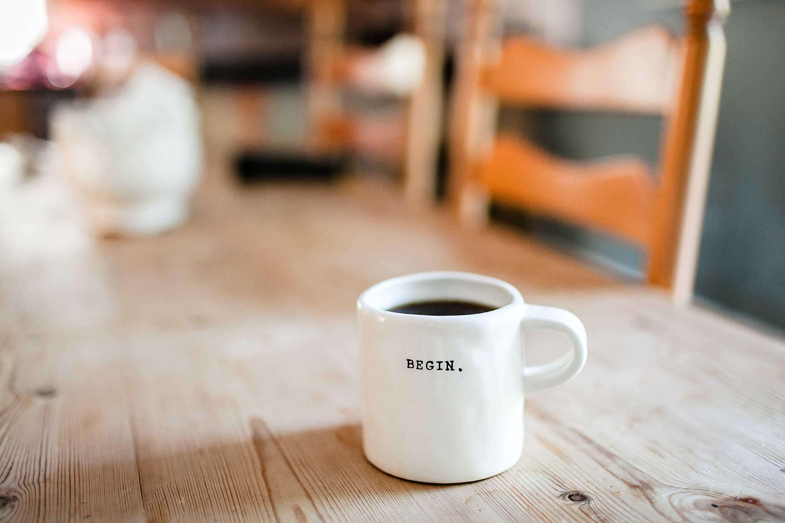 """Against a blurred table and chairs background, a white coffee cup with black type saying """"Begin.""""."""